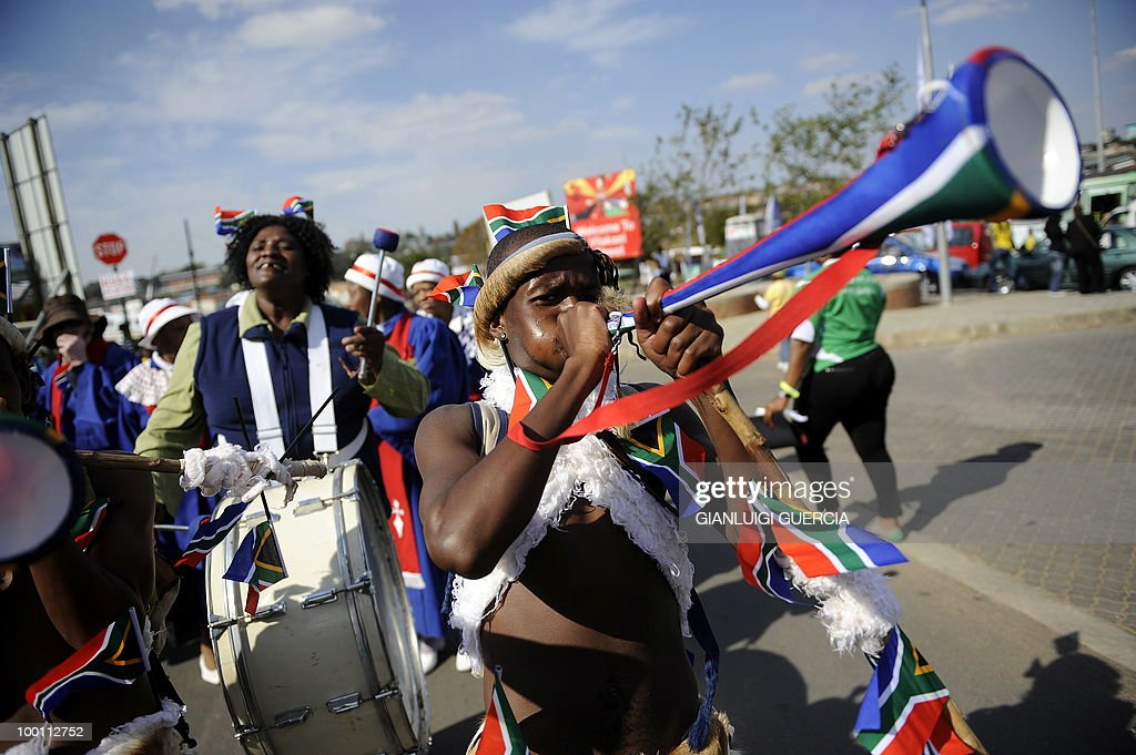 A dancer blows his vuvuzela (large coloured plastic trumpet) as minstrels parade on May 21, 2010 during the official celebration marking 20 days ahead of the FIFA WC2010 kick off at Vilakazi street in Soweto, South Africa. South Africa will host the FIFA World Cup from the 11 of June to the 11 of July, 2010.