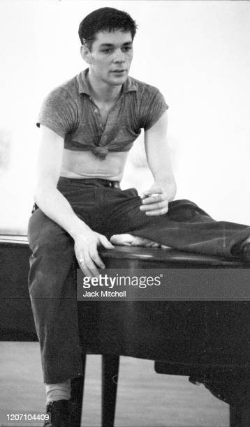 Dancer Dirk Sanders sits atop a piano during backstage rehearsals for Mary Martin's Easter Sunday live color telecast 1959