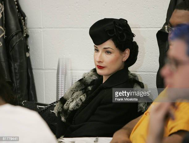 """Dancer Dita Von Teese listens to fiance musician Marilyn Manson as he speaks to students at Temple University's """"Art & Society"""" class during a taping..."""