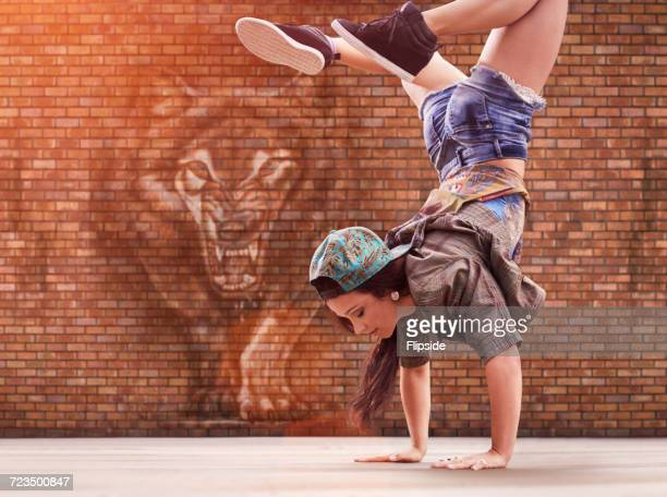 Dancer doing back flip, tiger street art in background