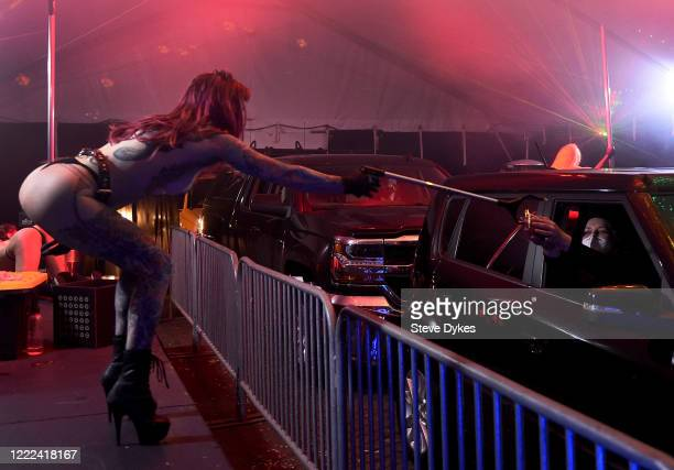 Dancer Elle uses an extension tool to accept a tip from patrons during the Drive-thru at The Lucky Devil on May 01, 2020 in Portland, Oregon. The...