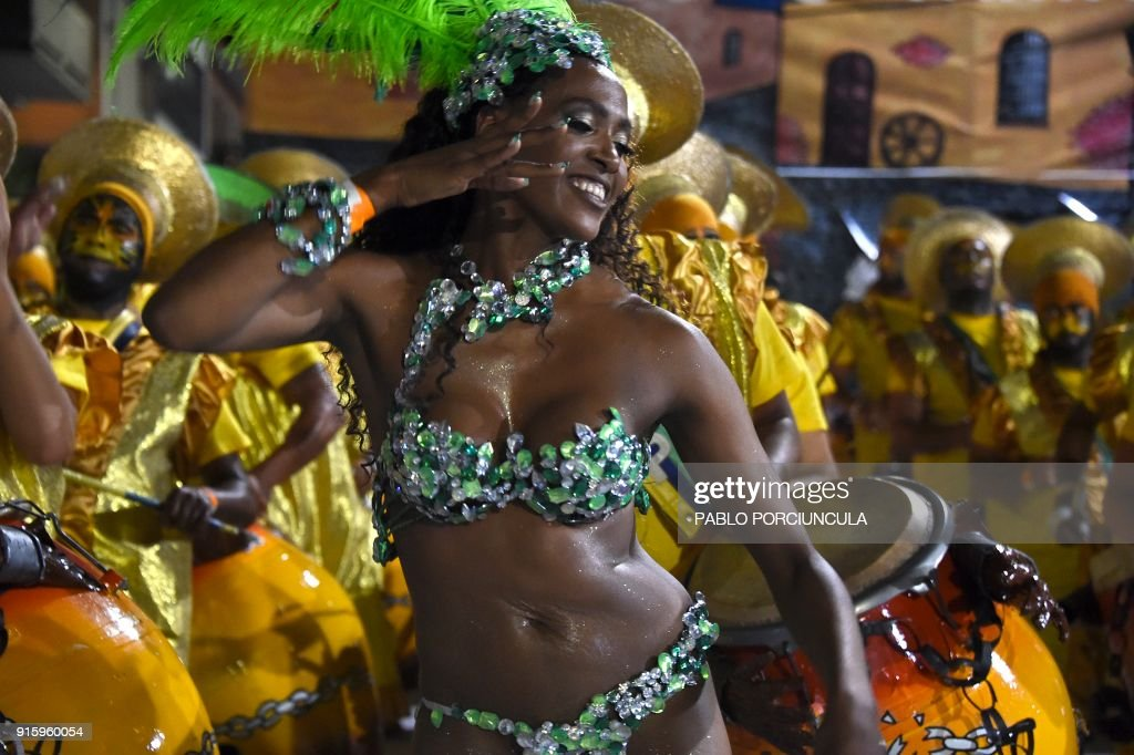 A dancer forming part of a group known as a 'comparsa' competes by dancing to the rhythm of the traditional 'candombe' music, in Montevideo on February 8, 2018, during the 'Llamadas', one of the events that make up Uruguay's carnival -- the world's longest. / AFP PHOTO / Pablo PORCIUNCULA