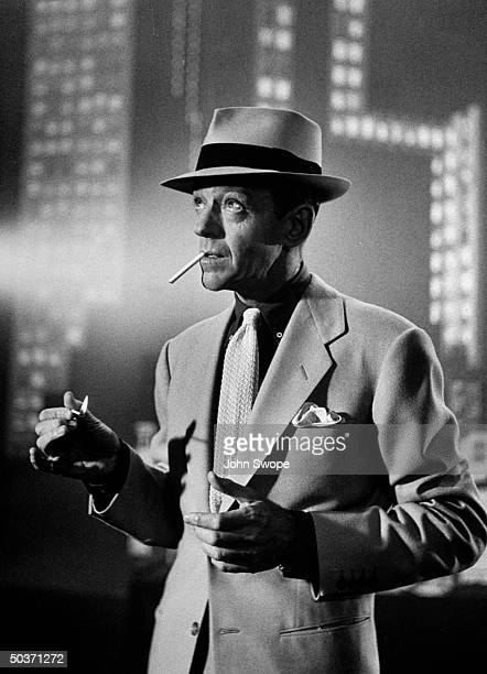 Dancer Fred Astaire lighting cigarette in dance number that is a parody of a Mickey Spillane scene in the movie The Band Wagon