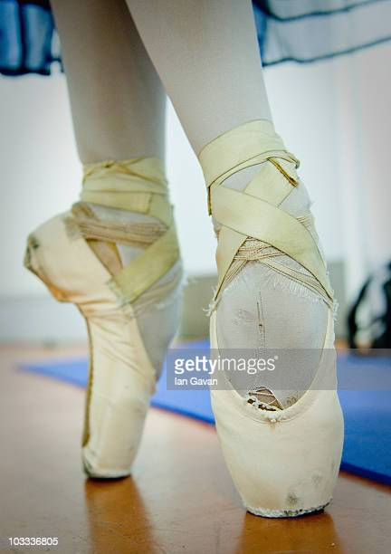 A dancer from the English National Ballet prepares her pointe shoes back stage prior to a dress rehearsal of Cinderella at the Coliseum on August 10...
