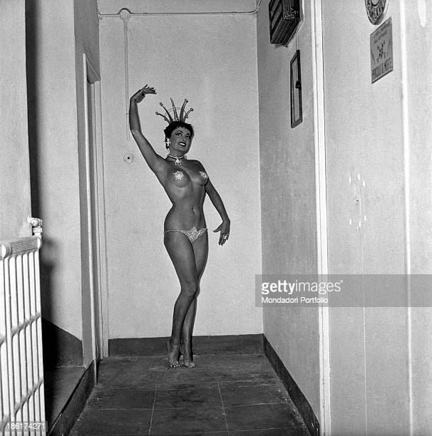 A dancer from the famous company Folies Bergère in a scanty scenic dress and barefoot poses in the corridors of a theatre Italy 1953