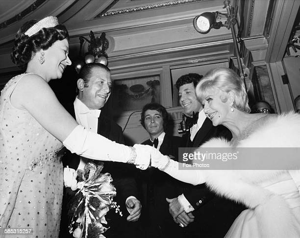 Dancer Ginger Rogers curtseys as she greets Queen Elizabeth II after the Royal Variety Performance at the London Palladium, November 10th 1969.