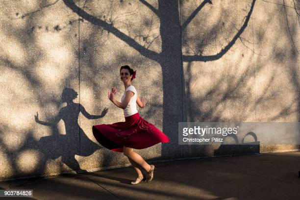 A dancer goes through here routine in front of a shadow speckled wall.