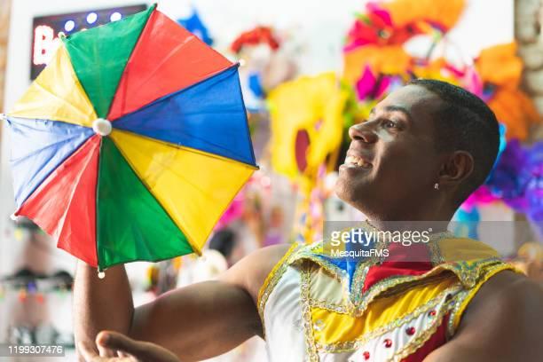 danseur retenant un parasol coloré - gogo danseuse photos et images de collection