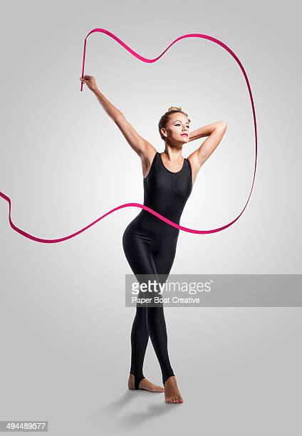 Dancer holding a long pink ribbon in the studio