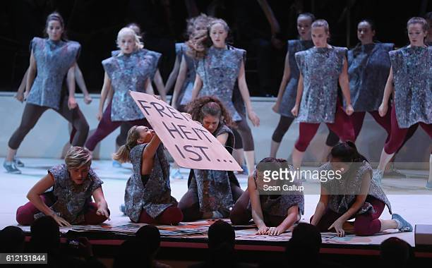 A dancer holds up a sign that reads 'Freedom is ' during a performance during celebrations to mark German Unity Day at the Semperoper opera house on...