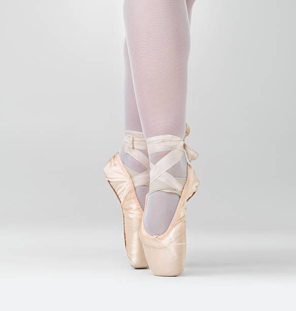 Dancer in ballet shoes dancing in Pointe against white