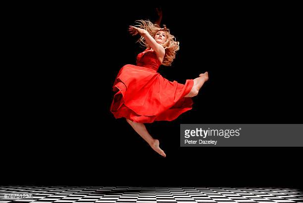 dancer in red dress in the air - red dress stock pictures, royalty-free photos & images