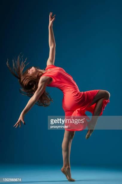 danseur dans la robe rouge sur le fond bleu - gymnastique au sol photos et images de collection