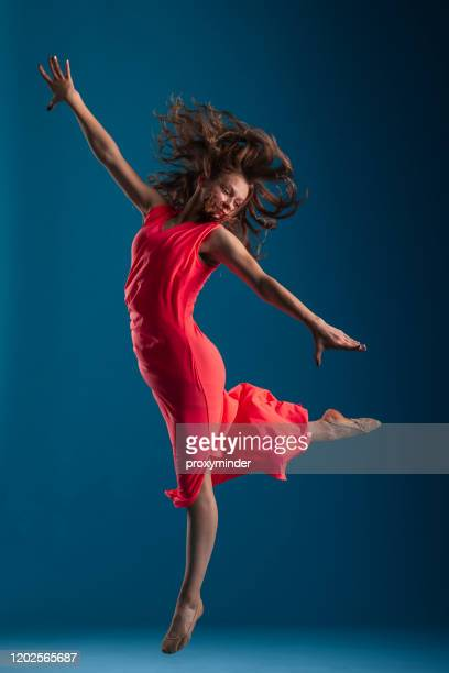 dancer in red dress on blue background - red dress stock pictures, royalty-free photos & images