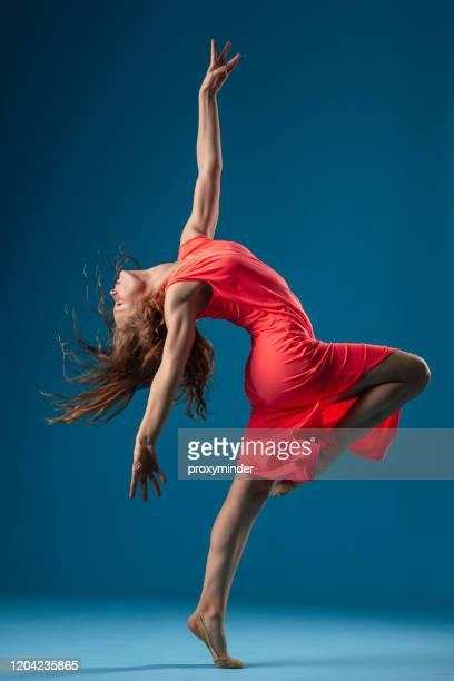 青い背景に赤いドレスのダンサー - 赤のドレス ストックフォトと画像