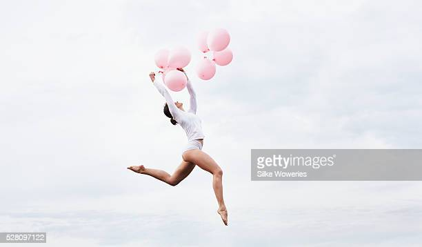 dancer jumping high in the air holding pink balloons