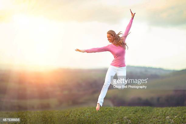Dancer Jumps over Countryside Landscape