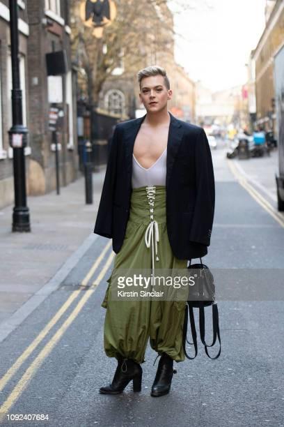 Dancer Kolton Krouse wears a Sartoria Correale jacket Adidas bag Fenty trousers Coach boots during London Fashion Week Men's January 2019 on January...