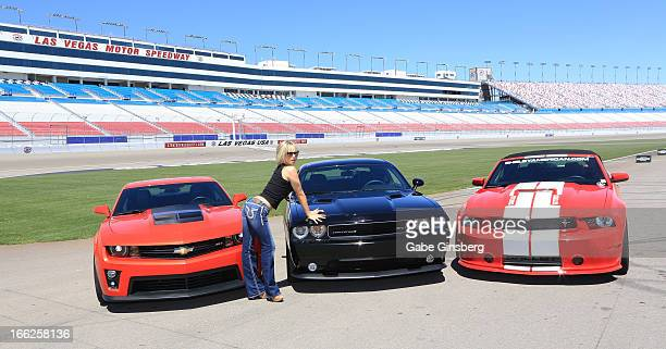Dancer Kristin Ratatori from the show 'Fantasy' poses in front of Chevrolet Camero ZL1 Dodge Challenger SRT8 392 and a Ford Mustang Shelby GT350 at...