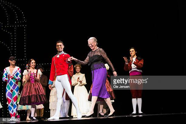 A dancer leads Queen Margrethe on to the stage where she and the ballet company receive the audiences standing ovations at the premiere evening of...