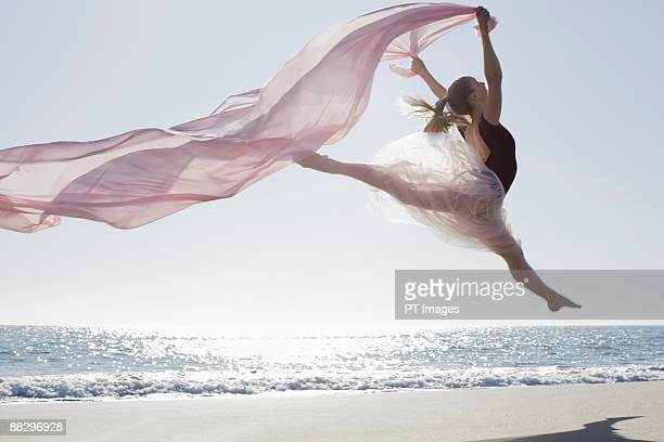 Dancer leaping on beach