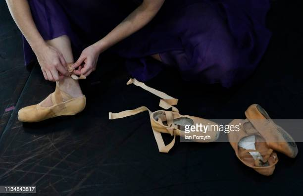 A dancer makes final adjustments to her ballet shoes as she waits on stage before the curtain goes up at the World Premier of Northern Ballet's...