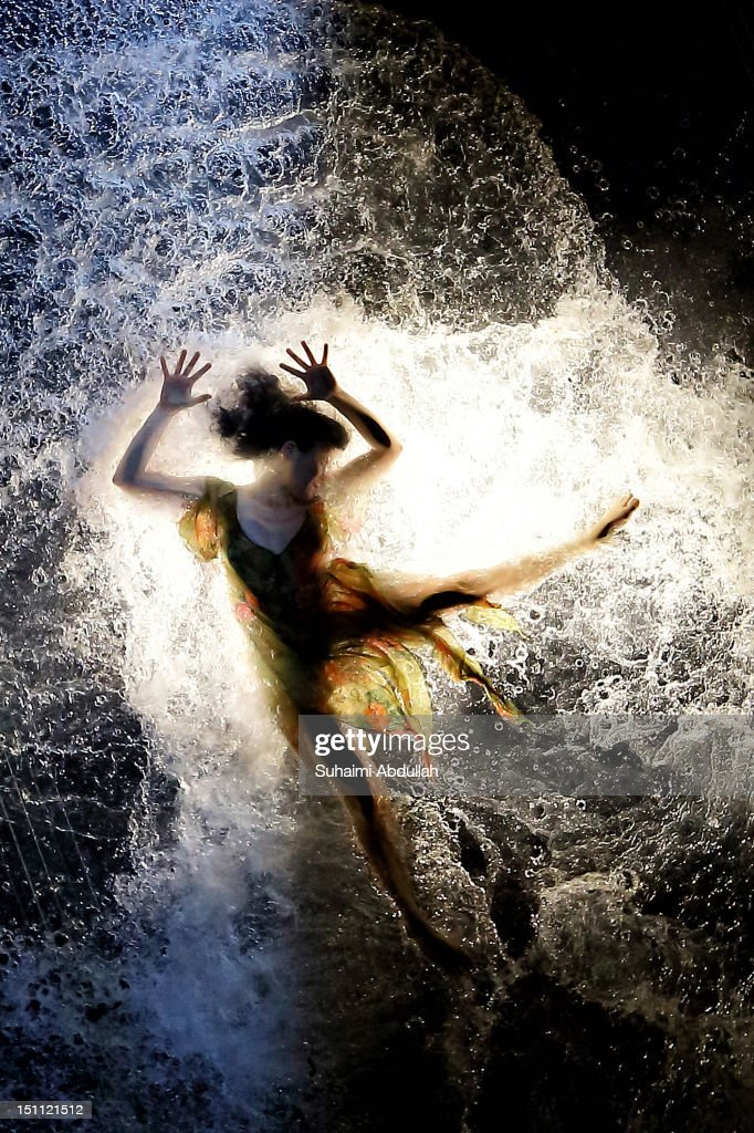 A dancer of acclaimed Argentinian group Fuerzabruta performs in a piece entitled 'Mylar', while being suspended on a translucent 15m pool during Singapore's 5th annual Night Festival on September 1, 2012 in Singapore.