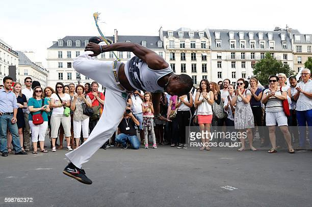A dancer of the Bahia Sud band performs Capoeira during the Brazilian Cultural Festtival 'Lavage de la Madeleine' on September 2 2016 in front of the...