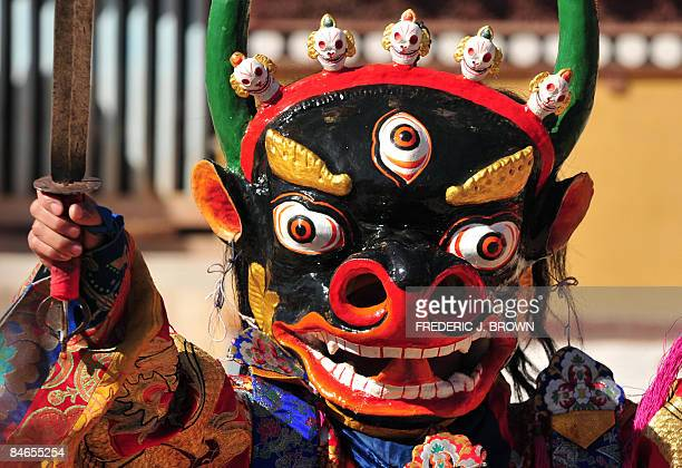 A dancer peers though an opening in his mask while performing for a crowd gathered to watch Cham Dances during ongoing festivities celebrating Monlam...