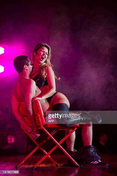A dancer performs a strip dance with a spectator during a strip dance contest during the Erotika Fair in Sao Paulo Brazil on March 25 2012 The annual...