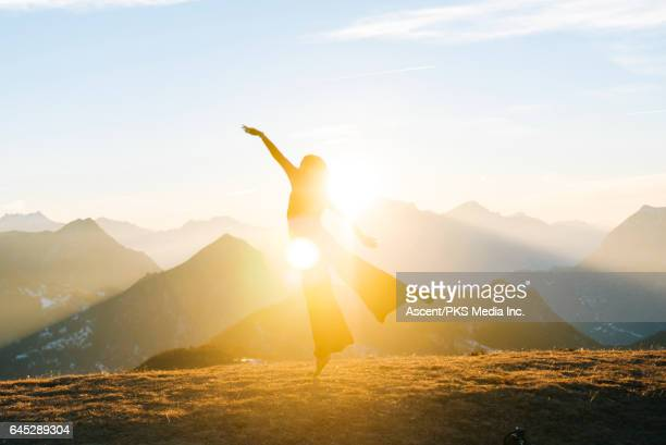 Dancer performs moves on mountain summit, sunrise
