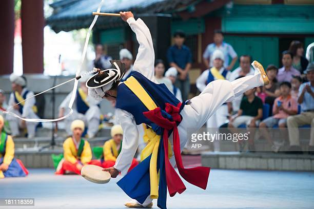 A dancer performs the jumping dance 'Poongmul' at a Seoul yard designed for traditional plays in Seoul on September 19 2013 This acrobatic...