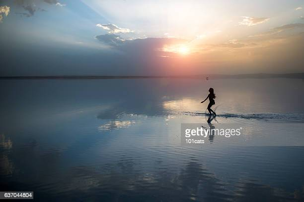 Dancer running on the lake in the evening