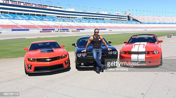 Dancer Ryan Paki from the show 'Thunder Down Under' poses in front of Chevrolet Camero ZL1 Dodge Challenger SRT8 392 and a Ford Mustang Shelby GT350...