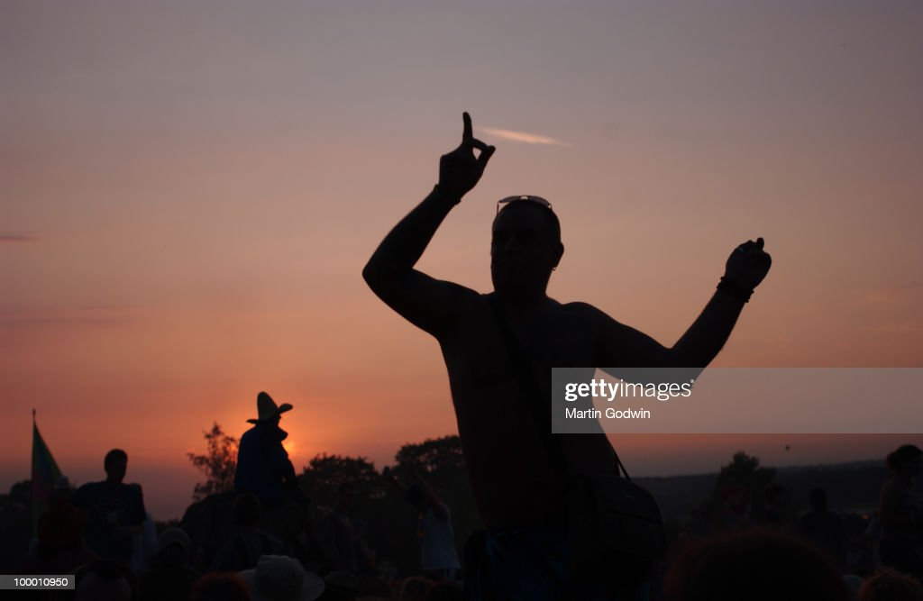 Dancer silhoueted against the setting sun at Glastonbury, 23rd June 2005.
