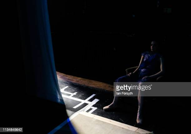 A dancer sits in a chair and rests as she exits the stage during the World Premier of Northern Ballet's performance of 'Victoria' at Leeds Grand...
