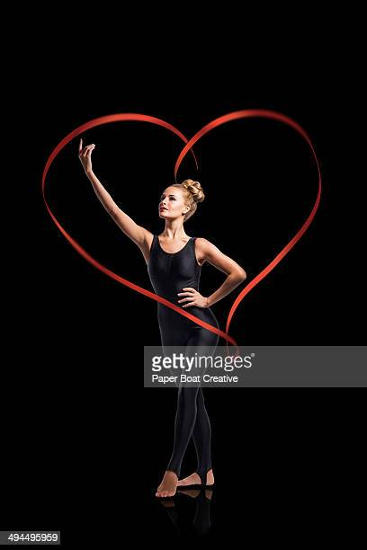 Dancer standing in the middle of a heart ribbon