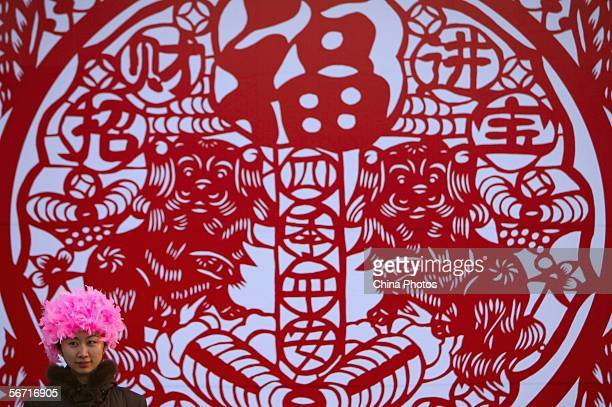 A dancer stands in front of a wall decorated with giant papercut featuring dogs and good wishes during Longtan Lake new year temple fair on February...