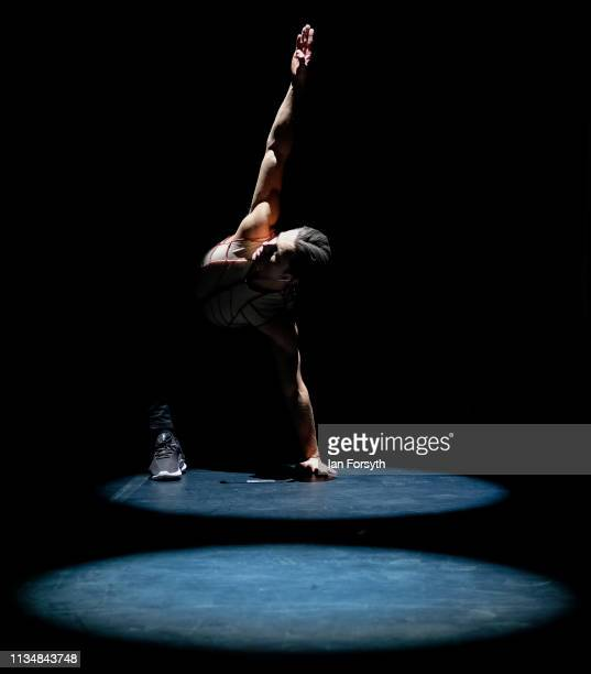 A dancer stretches on stage as he warms up minutes before the curtain goes up for the World Premier of Northern Ballet's performance of 'Victoria' at...