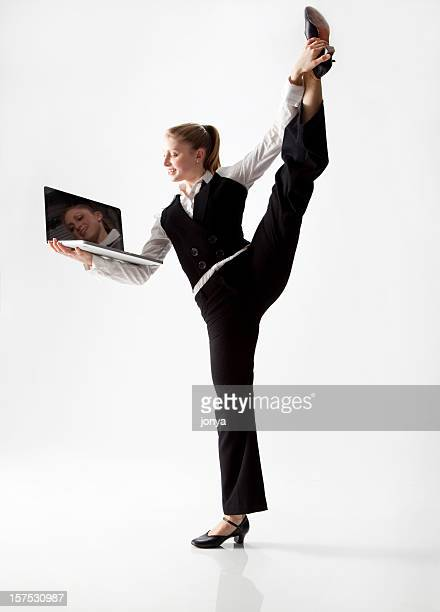 dancer stretching her leg with one hand, holding laptop