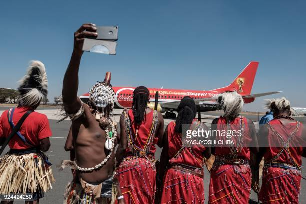 TOPSHOT A dancer takes a selfie upon the arrival of the special aircraft carrying the FIFA World Cup Trophy during its World Tour on February 26 2018...