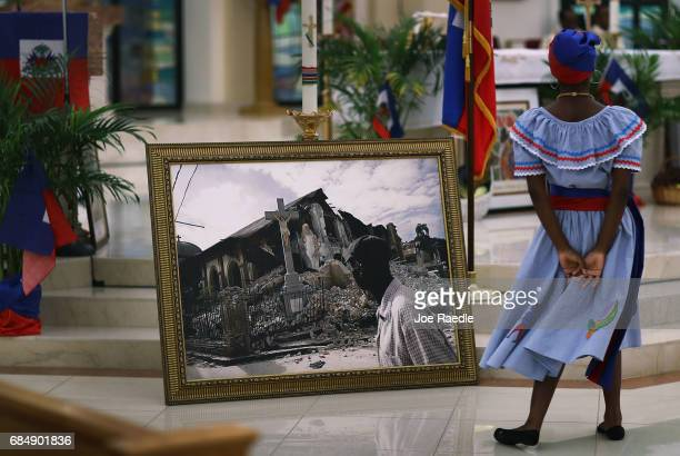 A dancer takes part in a dance near a framed picture of a church that was destroyed by the massive 2010 Earthquake in Haiti during a service at the...