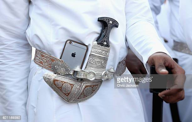 A dancer tucks his Apple iphone next to his traditional Omani dagger during an Omani cultural welcome ceremony outside the Sultan's Palace on the...