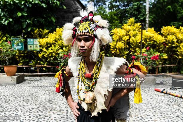 A dancer wearing an Iban warrior traditional costume waits for the arrival of Britain's Prince Charles and his whfe Camilla Duchess of Cornwall at...