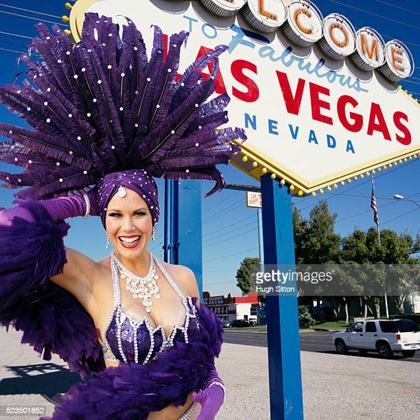 dancer with headdress standing in front of las vegas sign - hugh sitton stock pictures, royalty-free photos & images