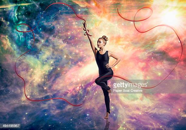 Dancer with long red ribbon against cosmic sky