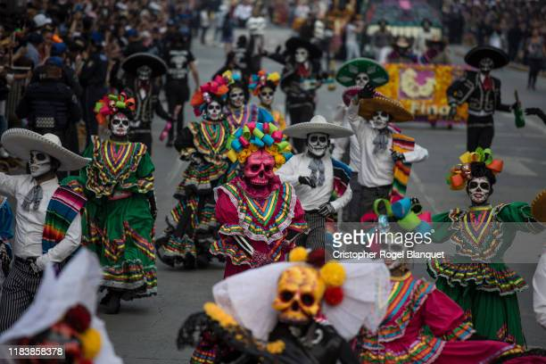 Dancers and dancers characterized as Catrinas perform during the Day of the Dead Parade in Mexico City on October 27 2019 in Mexico City Mexico...