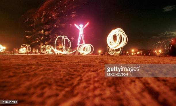 Dancers at the 'Burning Man' festival create patterns with fireworks in the Black Rock Desert of Nevada just prior to burning a fivestory neonlit...