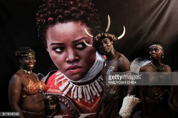 Dancers from Kenya's Luo tribe pose in front of an image of Kenyan actress Lupita Nyong'o before the African premier of the Marvel film 'Black...