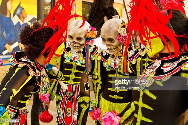 CONTENT] Dancers in Aztecthemed yellow red and black costumes with skeleton masks at the Dia de los Muertos Parade Milwaukee WI